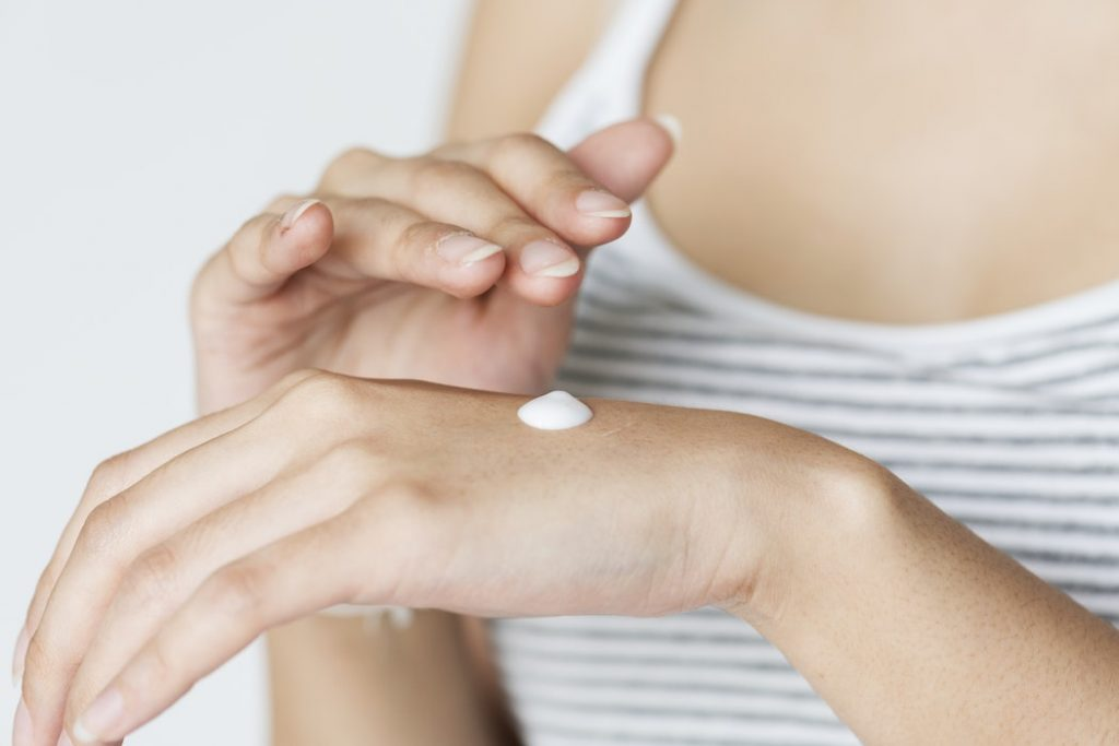 A person rubbing cream on the back of their hand.